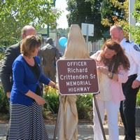 Widow Christine Crittenden and daughter Stacy Aason unveil sign
